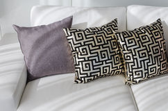 Guld- kuddar med den kinesiska modellen utformar på den vita soffan Royaltyfri Foto