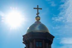 Guld- kupol och ett kors på en bakgrund av blå himmel och ljust solljus Arkivfoto