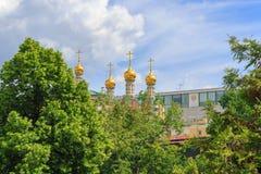 Guld- kupoler av den Verkhospasskiy domkyrkan i MoskvaKreml på en bakgrund för blå himmel i solig sommardag arkivbild