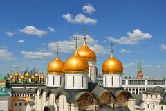 Guld- kupoler av domkyrkor av MoskvaKreml på bakgrund för blå himmel arkivbild
