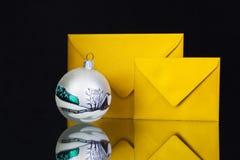 Guld- kuvert och julgarnering på det svarta glass skrivbordet Royaltyfria Bilder