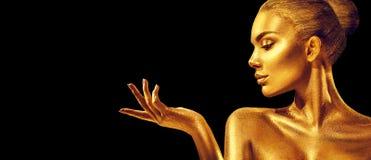 guld- kvinna Flicka för skönhetmodemodell med guld- hud, makeup, hår och smycken på svart bakgrund royaltyfri foto
