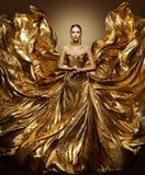 Guld- kvinnaflygklänning, modemodell i vinkande guld- kappa för konst royaltyfria foton