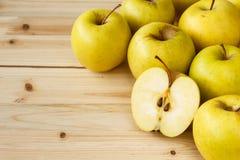Guld- - läckra äpplen på en träbakgrund Arkivfoto