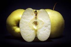 Guld- - läckra äpplen på svart bakgrund arkivfoton