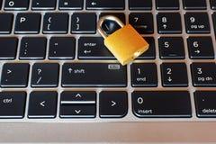 Guld- låst hänglås på bärbar datortangentbordet royaltyfri bild