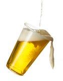 Guld- lager eller öl i disponibel plast- kopp Arkivbild