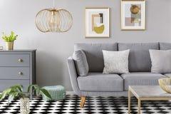 Guld- lampa i grå vardagsruminre med affischen ovanför grå färger så royaltyfri bild