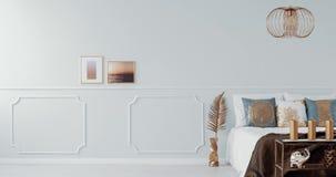 Guld- lampa ovanför en säng i ljus sovruminre med den guld- fåtöljen video arkivfilmer