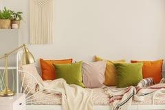 Guld- lampa på nightstanden bredvid olivgrön gräsplan, pastellfärgade rosa, gula och orange kuddar på enkel metallsäng med mönstr royaltyfri foto