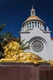 Guld- lejonstaty framme av kyrkan Royaltyfria Bilder