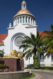 Guld- lejonstaty framme av kyrkan Arkivfoto
