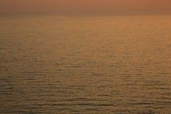 Guld- ljus reflexion för solnedgång på bakgrund för yttersida för havsvågkrusning Abstrakt begrepp lugn, loppet, serenitet, roman arkivfoto