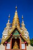 Guld- ljust skina på den vita och guld- pagoden under soluppgång/solnedgång med blå himmel Arkivfoto