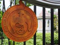 Guld- logo av myntmuseet, Bangkok, på järnstaketet royaltyfria bilder