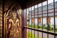 Guld-målad Buddhabild på en träslutare inom den huvudsakliga Wiharnen av Wat Chiang Man, Chiang Mai, Thailand Arkivbilder