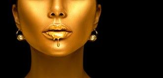 Guld- målarfärg dryper från de sexiga kanterna, guld- vätskedroppar på härlig mun för modellflicka` s, idérik abstrakt makeup royaltyfria bilder