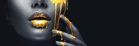 Guld- målarfärg smetar droppander från framsidakanterna och handen, guld- vätskedroppar på härlig modellflickmun, idérik makeup royaltyfri fotografi
