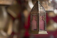 Guld mönstrade lampan som hänger från taket av ett lager i en Marrakech souk arkivbild