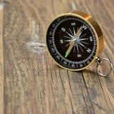 Guld- magnetisk kompass på det Wood brädet Royaltyfria Bilder