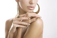 Guld- manikyr, kvinnlighänder med skinande guld- spikar polermedel Arkivfoto