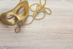 Guld- Mardi Gras maskeringar och pärlor på en träbakgrund fotografering för bildbyråer