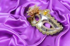 Guld- maskera på purpurfärgat silk tyg Arkivbild