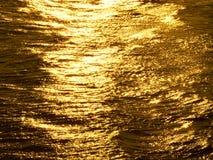 Guld- Melt Vatten på solnedgång Släta krusningar Arkivfoto