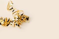 Guld- metalliskt lockigt band på en kräm- bakgrund Arkivfoton