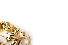 Guld- metalliskt lockigt band på en kräm- bakgrund Royaltyfri Bild