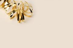 Guld- metalliskt lockigt band på en kräm- bakgrund Arkivbilder