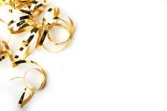 Guld- metalliskt lockigt band på en vit bakgrund Arkivbild