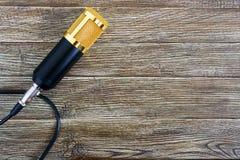 Guld- mikrofon för kondensator med kabel på en trätabell med kopieringsutrymme musikaliskt tema royaltyfria bilder
