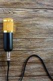 Guld- mikrofon för kondensator med kabellögner på en trätabell med kopieringsutrymme musikaliskt tema Lekmanna- lägenhet arkivbilder