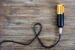 Guld- mikrofon för kondensator med kabellögner på en trätabell med kopieringsutrymme musikaliskt tema Lekmanna- lägenhet arkivfoton