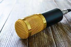 Guld- mikrofon för kondensator på en trätabell Ljuset från vänster sida royaltyfri foto