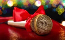Guld- mikrofon med den röda pilbågen Royaltyfri Foto