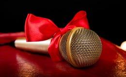 Guld- mikrofon med den röda pilbågen Royaltyfri Bild