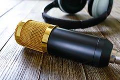Guld- mikrofon- och hörlurarlögner för kondensator på en trätabell arkivfoto