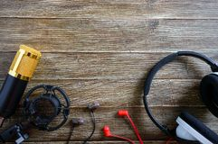 Guld- mikrofon- och hörlurarlögner för kondensator på en trätabell med kopieringsutrymme musikaliskt tema royaltyfri bild