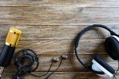 Guld- mikrofon- och hörlurarlögner för kondensator på en trätabell med kopieringsutrymme musikaliskt tema royaltyfria foton