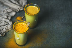 Guld- mjölka med gurkmejapulver i exponeringsglas över grungebakgrund Fotografering för Bildbyråer