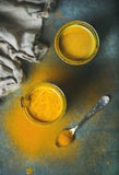 Guld- mjölka med gurkmejapulver i exponeringsglas över mörk bakgrund Royaltyfria Foton