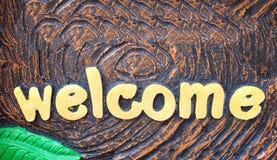 Guld- modeller för välkommet tecken för målarfärgalfabet som är abstrakta på bakgrund royaltyfri foto