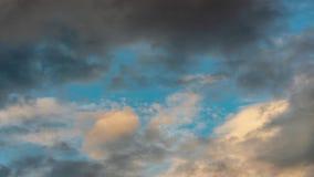 Guld- moln och mörka åskmoln som svävar över solig blå himmel Tid schackningsperiod stock video
