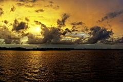 Guld- molnig solnedgångSeascape med reflexioner för havsvatten Royaltyfria Foton