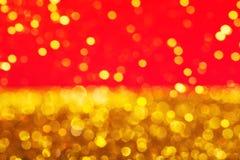 Guld- mousserande bokeh samman med röd abstrakt bakgrund arkivbilder