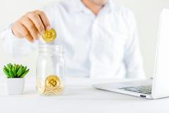 Guld- mynt för Bitcoin mynt i den glass kruset på trätabell, manH royaltyfri fotografi