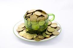 Guld- mynt i en kopp Arkivfoto
