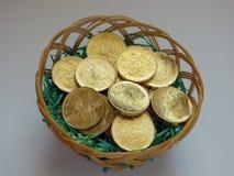 Guld- mynt i korg Royaltyfri Bild